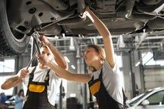 Профессиональные механики стоя под автомобилем и работой стоковое фото rf