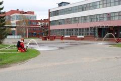 Профессиональные пожарные в оранжевых огнезащитных костюмах в белых шлемах с масками противогаза испытывают пожарные рукава и ору стоковая фотография rf