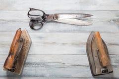 Профессиональные старые большие утюги портноя и большие ножницы одно на ru стоковая фотография rf