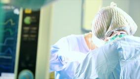 Профессиональные хирурги и ассистенты обсуждают деятельность во время ее Они работают в современной операционной больницы акции видеоматериалы