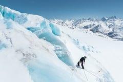 Профессиональный альпинист в шлеме и лыжной маске на страховании делает забоин-отверстие в леднике против фона стоковое фото