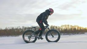 Профессиональный весьма велосипедист спортсмена ехать жирный велосипед в outdoors Езда велосипедиста в зиме на льде снега Человек сток-видео