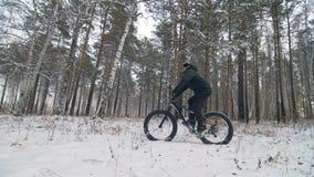 Профессиональный весьма велосипедист спортсмена ехать жирный велосипед в outdoors Езда велосипедиста в человеке леса снега зимы д сток-видео
