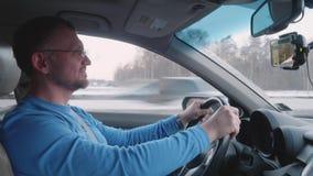 Профессиональный водитель на руле на шоссе на высокой скорости усмехаясь и слушая для того чтобы укомплектовать личным составом о сток-видео