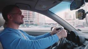 Профессиональный водитель управляет автомобилем в городе на дороге со зданиями на предпосылке акции видеоматериалы
