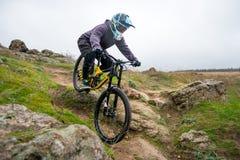 Профессиональный горный велосипед катания велосипедиста вниз с скалистого холма Весьма спорт и концепция Enduro велосипед Стоковое Изображение
