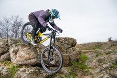 Профессиональный горный велосипед катания велосипедиста вниз с скалистого холма Весьма спорт и концепция Enduro велосипед Стоковые Фото