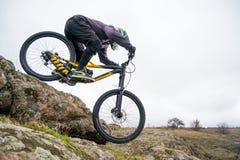 Профессиональный горный велосипед катания велосипедиста вниз с скалистого холма Весьма спорт и концепция Enduro велосипед Стоковое Изображение RF