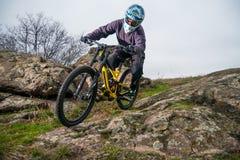 Профессиональный горный велосипед катания велосипедиста вниз с скалистого холма Весьма спорт и концепция Enduro велосипед Стоковая Фотография