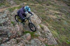 Профессиональный горный велосипед катания велосипедиста вниз с скалистого холма Весьма спорт и концепция Enduro велосипед Стоковые Фотографии RF