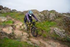 Профессиональный горный велосипед катания велосипедиста вниз с скалистого холма Весьма спорт и концепция Enduro велосипед Стоковые Изображения RF