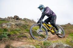 Профессиональный горный велосипед катания велосипедиста вниз с скалистого холма Весьма спорт и концепция Enduro велосипед Стоковое Фото