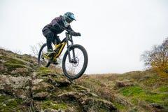 Профессиональный горный велосипед катания велосипедиста вниз с скалистого холма Весьма спорт и концепция Enduro велосипед Стоковые Изображения