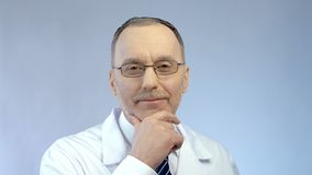 Профессиональный доктор усмехаясь добросердечно, представляющ для камеры, качественные обслуживания клиники стоковая фотография rf