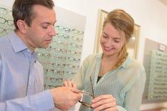 Профессиональный женский клиент порции optician для того чтобы выбрать зрелища стоковое изображение rf
