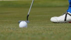 Профессиональный игрок в гольф кладя шарик в отверстие Шар для игры в гольф краем отверстия с игроком в предпосылке на солнечный  Стоковая Фотография RF