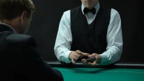 Профессиональный крупье шаркая карточки на зеленой таблице для бизнесмена, игры в покер сток-видео