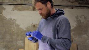 Профессиональный мастер с бородой и усиком красит деревянное пятно с губкой внутри помещения Деревянная картина 4 k акции видеоматериалы