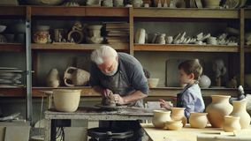 Профессиональный мужской гончар работает с глиной на закручивая бросать-колесе при его любознательный внук помогая ему керамическ сток-видео
