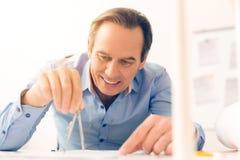Профессиональный мужской инженер держа пару компасов стоковое фото