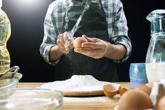 Профессиональный мужской повар брызгает тесто с мукой, preapares или печет хлеб на кухонном столе стоковое фото rf
