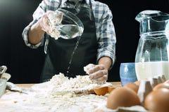 Профессиональный мужской повар брызгает тесто с мукой, preapares или печет хлеб на кухонном столе стоковые изображения rf