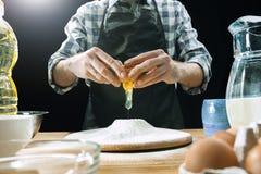 Профессиональный мужской повар брызгает тесто с мукой, preapares или печет хлеб на кухонном столе стоковое изображение rf