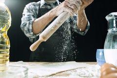 Профессиональный мужской повар брызгает тесто с мукой, preapares или печет хлеб на кухонном столе стоковая фотография rf