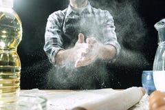 Профессиональный мужской повар брызгает тесто с мукой, preapares или печет хлеб на кухонном столе стоковое изображение