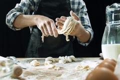 Профессиональный мужской повар брызгает тесто с мукой, preapares или печет хлеб на кухонном столе стоковые фотографии rf