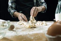 Профессиональный мужской повар брызгает тесто с мукой, preapares или печет хлеб на кухонном столе стоковые фото