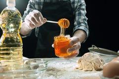 Профессиональный мужской повар брызгает тесто с мукой, preapares или печет хлеб на кухонном столе стоковые изображения