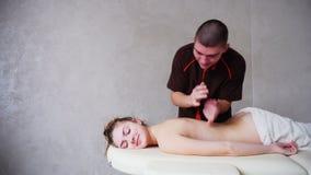 Профессиональный мужской masseur замешивает ` s девушки назад к пациенту, который лежит на кресле в ярком офисе акции видеоматериалы