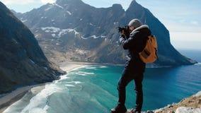 Профессиональный мужчина фотографа принимая фотоснимок долины с ландшафтом рюкзака DSLR нося фотографируя сценарным видеоматериал