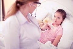 Профессиональный опытный доктор рассматривая меньшую больную девушку лежа в кровати стоковая фотография rf
