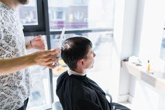 Профессиональный парикмахер с гребнем и ножницами в его руке вводя влажные черные и короткие волосы в моду человека в a стоковое фото rf