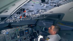 Профессиональный пилот регулирует различные переключатели на палубе арены самолета видеоматериал