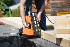 Профессиональный плотник используя пневматическое оружие ногтя стоковые фотографии rf