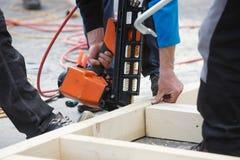 Профессиональный плотник используя пневматическое оружие ногтя стоковая фотография