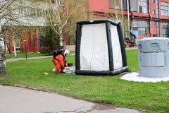 Профессиональный пожарный в оранжевом специальном пожаробезопасном костюме подготавливает собрать белый шатер кислорода к людям с стоковое фото rf