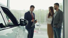 Профессиональный продавец автомобиля в костюме имеет переговор при привлекательные богатые пары говоря им о новом автомобиле видеоматериал