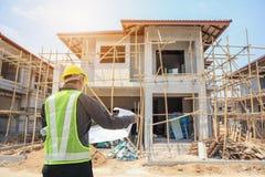 Профессиональный работник архитектора инженера с защитной бумагой шлема и светокопий стоковые фото
