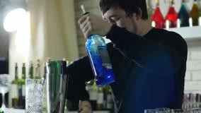 Профессиональный работник бара льет покрашенные ликеры от бутылок с тонкой шеей в шейкер металла акции видеоматериалы