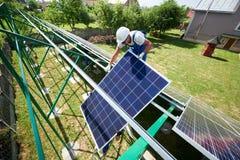 Профессиональный работник устанавливая панели солнечных батарей на зеленую конструкцию металла стоковое фото