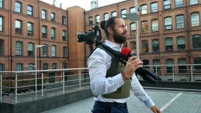 Профессиональный репортер в реальном маштабе времени на улице города Репортер с особенными одеждами идет через улицы города акции видеоматериалы
