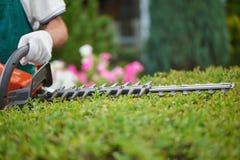Профессиональный садовник, работая с equipmentl сада стоковое фото