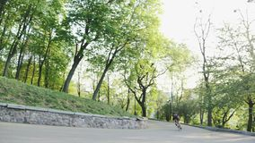 Профессиональный сильный тощий всадник велосипеда спуская на curvy дорогу нося черный jersey и шорты Велосипедист идя вниз с холм сток-видео