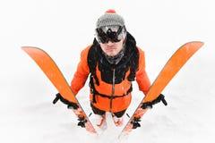 Профессиональный спортсмен лыжника в оранжевом черном костюме с черной лыжной маской с лыжами в его стойках рук с a стоковые изображения rf