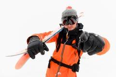 Профессиональный спортсмен лыжника в связанной шляпе и оранжевый черный костюм с черной лыжной маской с лыжами на его пунктах пле стоковое изображение rf