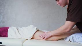 Профессиональный терапевт массажа парня вручную делает массажем ноги анти--целлюлита женского пациента который лежит на кресле в  акции видеоматериалы